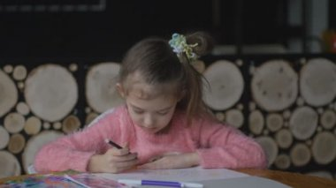 Little pretty girl draws with colored markers at table in room