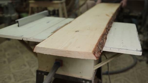 Muž vyjme obrovské dřevěné desce s stacionární Pily kotoučové