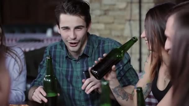 The guy in the company of friends animatedly tells an interesting story. The company drinks beer in a restaurant