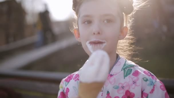 Malá dívka jí olizuje kužel zmrzliny na portrét lavička park