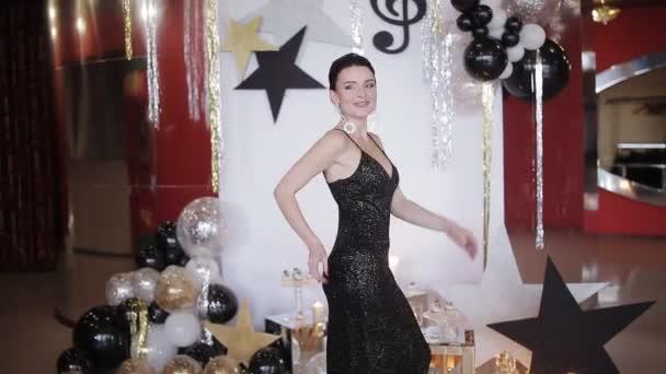 Sexy dívka ve večerních šatech tančí na večírku na slavnostní pozadí
