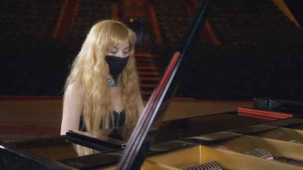 The woman with eyes of different colors in a black protective mask that hides her face, plays the piano in the concert hall.