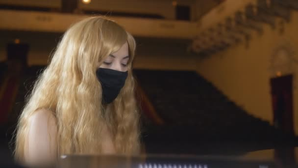 Unusual woman pianist in a black protective mask plays the piano in the concert hall.