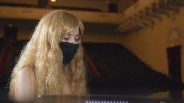 Ungewöhnliche Pianistin in schwarzer Schutzmaske spielt im Konzertsaal Klavier.