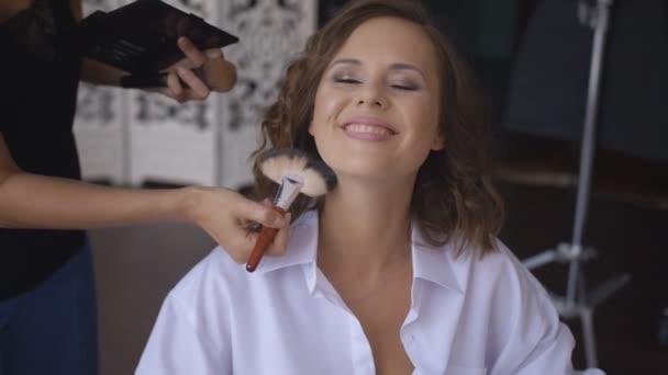 Visagistin pudert Gesicht zu fröhlich lachender Frau.
