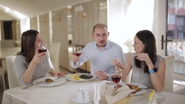 Opékání s červeným vínem před jídlem v restauraci světlé a vzdušné a přátel.