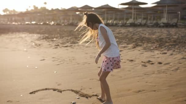 das kleine Mädchen am Strand zeichnet in den Sand.