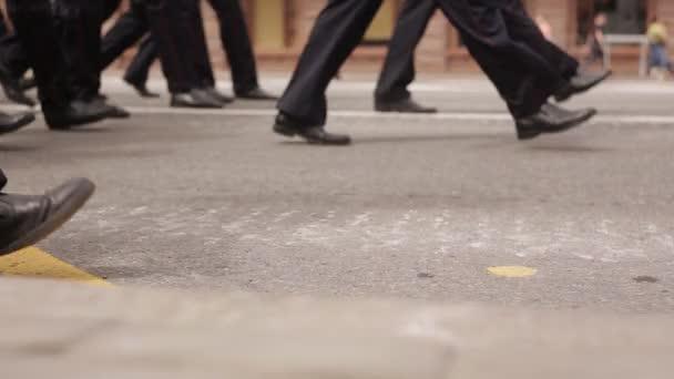 In blauen Uniformen und Schuhen laufen Polizisten in einer Gruppe.