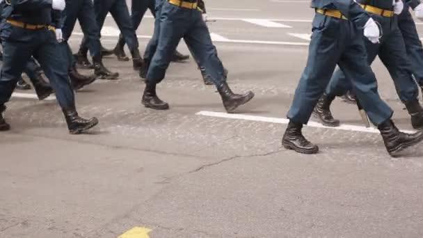 eine Nahaufnahme der Füße von Militärs, die auf der Parade marschieren. Gleiche Kleidung und Schuhe in der Öffentlichkeit. Militärmarsch in Zeitlupe aus nächster Nähe.