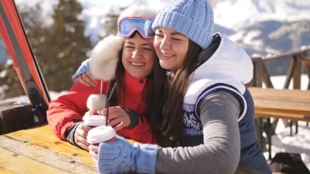 zwei glückliche Frauen in einem Café am Skigebiet kuscheln und gemeinsam Spaß haben.