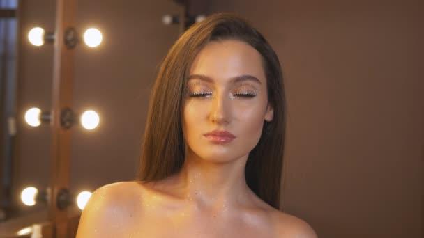 Žena s nahými rameny, usmívající se a pózující na kameru. Tvář Portrét detailní záběr sexy modelky s jasnou rtěnkou a kamínky kolem očí. Sexy žena tvář.