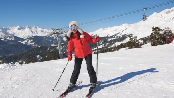 eine Frau im roten Skianzug auf der Piste, seitlich den Berg hinauf.