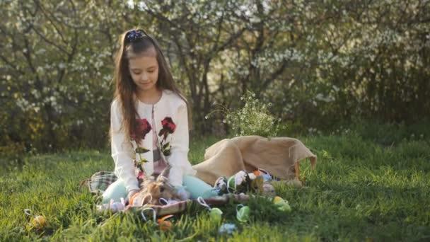 das Mädchen auf dem Hof sitzt auf dem Gras auf einem Hintergrund aus blühenden Bäumen und dekoriert mit bunten Eiern der Osterhase.