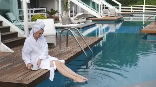 Elegant woman in white Bathrobe sitting on a pier by the pool in a luxury Villa and drinking coffee.