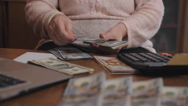 Egy idős nő nyilvántartást vezet a megtakarításokról. Egy idős nyugdíjas nő közeli kezei úgy hiszik, hogy a dollárszámlák.