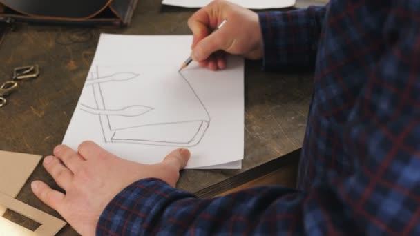 Currier rajzol egy vázlat bőr táskák munka előtt a műhelyben a bőr előállítására..