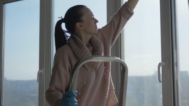 Žena stojící na žebříku myje panoramatická okna v bytě.