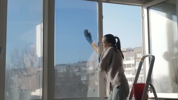 Žena je hospodyně v modrých rukavicích umýt velké panoramatické okna v bytě.
