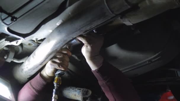 Professzionális autószerelő csavarozás részleteket autó speciális szerszám emelt autó javítóműhely közeli.