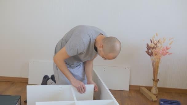 Muž, který doma montuje nábytek. Montáž nábytku na podlahu.