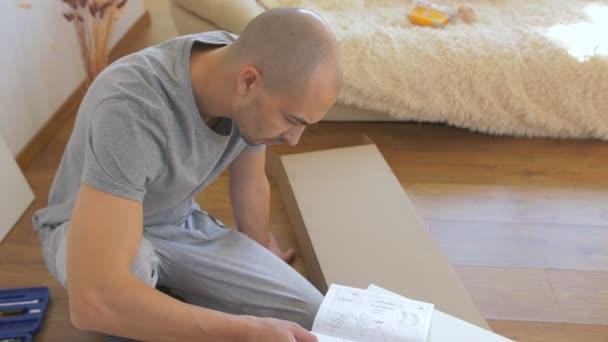 Ein Mann sitzt im Wohnzimmer auf dem Boden und liest die Montageanleitung für das Gestell.