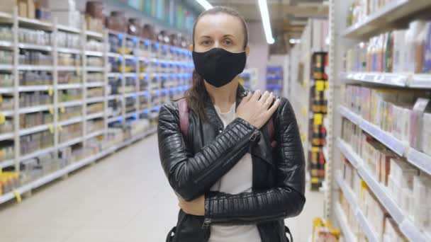 Žena v epidemiologické masce v supermarketu během pandemie koronaviru.