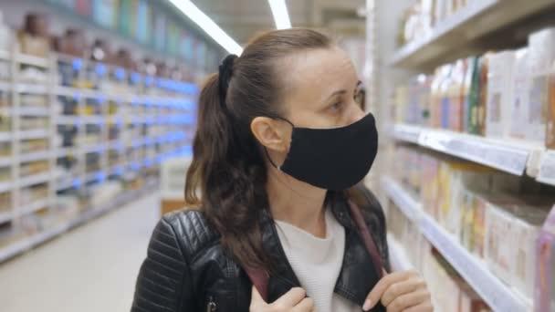 Eine Frau mit einer antiviralen Schutzmaske in einem Supermarkt wählt Produkte in den Regalen aus. Ein leerer Laden während der Quarantäne aufgrund der Pandemie.