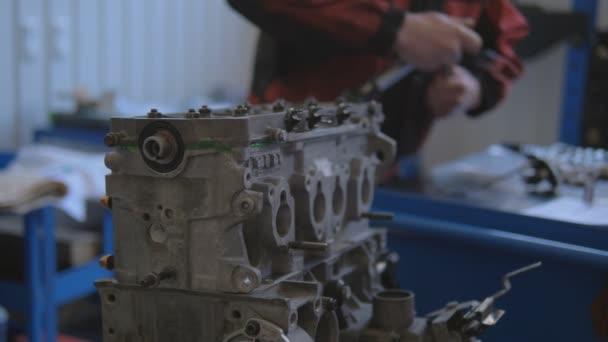 Samec automechanik se speciálním klíčem, šroub matice v automobilovém motoru. Osobní autoservisní stanice.