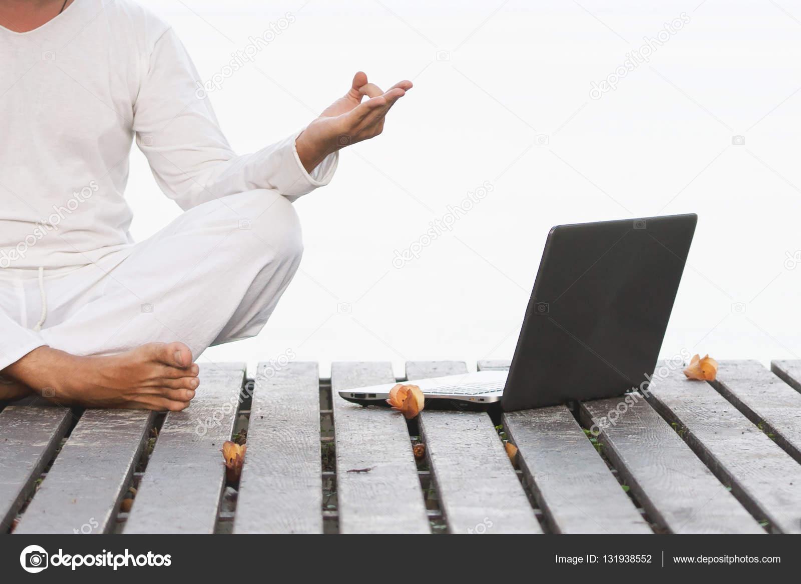 homme en v tements blancs m ditation yoga avec ordinateur portable sur la jet e en bois. Black Bedroom Furniture Sets. Home Design Ideas