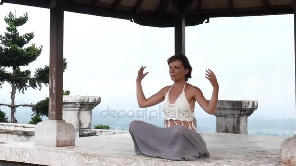 Žena medituje a dělá jógu v opuštěném chrámu. Ženská cvičná póza