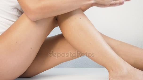 Žena s dokonalým tělem nanášení osvěžující krém nebo tělo na její nohy, pojem depilace, péče o pleť, kosmetika