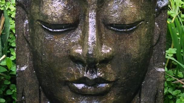 A trópusi kertben, Ubud, Bali, a csökkenő vízzel Buddha.