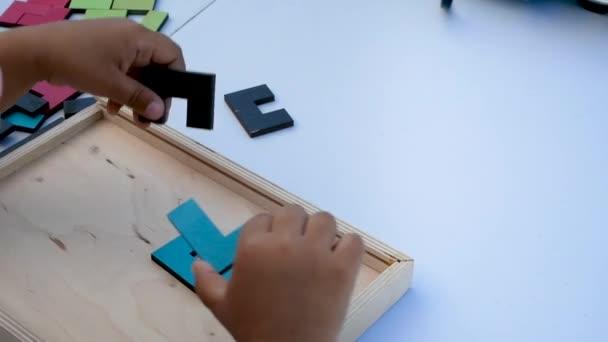 Pojem výchova dětí. Detailní Zpomalený pohyb. Ruka drží kus dřevěné kostky puzzle. Koncept komplexního a inteligentního logického myšlení.