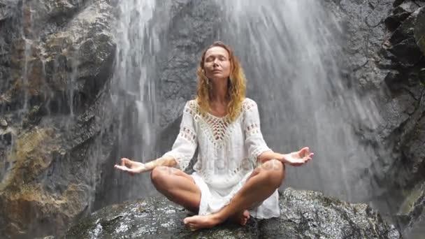 Frauen praktizieren Yoga am Wasserfall. HD-Video.