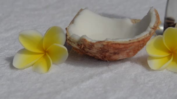 Flowers frangipani or plumeria, coconut and coconut massage oil on a white towel