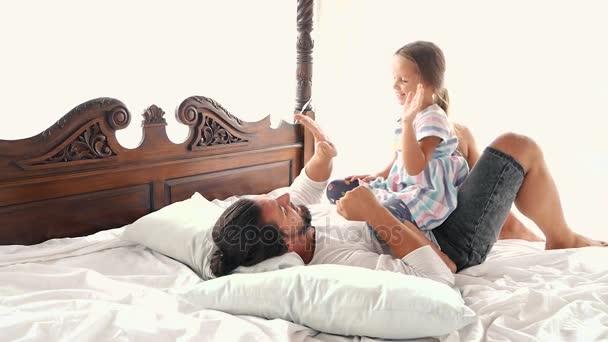 glückliches Familienidyll kleine Tochter springt Vater in die Arme und fällt auf ein Bett