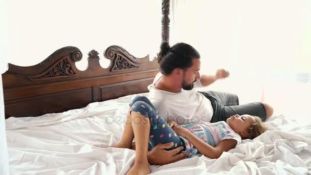 Šťastné rodinné idyly malé dítě dcera skočit na otce zbraně a spadnou na posteli
