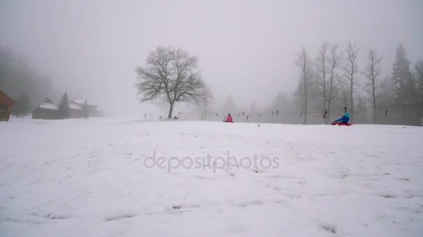 šťastná dívka a mather jezdí snowtube na zasněžených silnicích