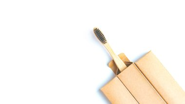 Bamboo toothbrush with black bristles in a paper box on a white background