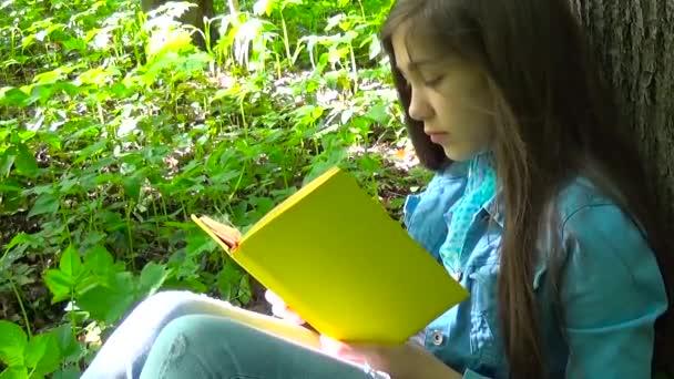 Portrét dospívající dívka čtení knihy a otáčení stránek opřený o kmen stromu v lese na jaře, studium venkovní. První vážné, pak se směje