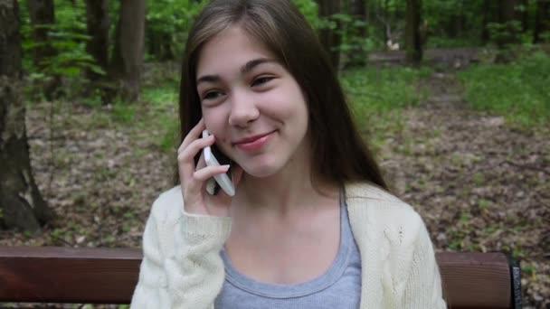 Mladá atraktivní dívka mluví do telefonu na lavičce. Letní park. Úsměv. HD video záběry natáčení statické kamery.