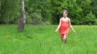 Teenager girl in orange dress running on a green meadow.