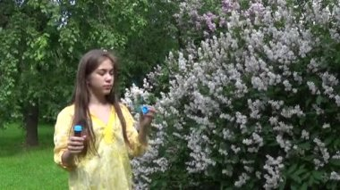 Beautiful teenager girl and soap bubbles. Video footage static camera.