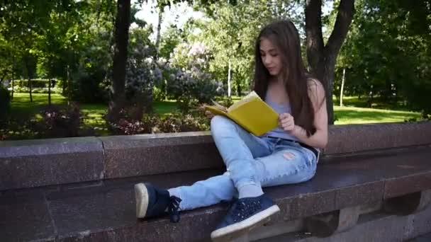 Roztomilý dospívající dívka čtení knihy sedí na lavičce v parku, studium venkovní. HD video záběry natáčení statické kamery