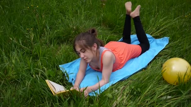 Uvolněná mladá dívka čtení knihy v poli. Cute teen ležící na trávě. Video záznam Hd natáčení statické kamery.