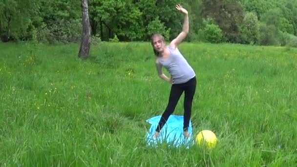 Young beautiful teenager girl in gray tank top practicing fitness exercising outdoors, in park in summer day. HD shooting panorama with steadicam.