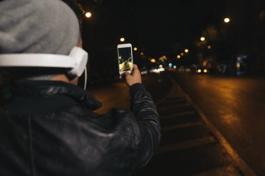 Boy takes a photograph of a street at night.