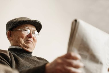 Elderly man reading a newspaper.