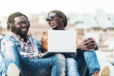 Two black race friends having fun with laptop.