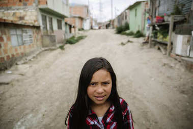 Portrait of cute girl in shanty town.